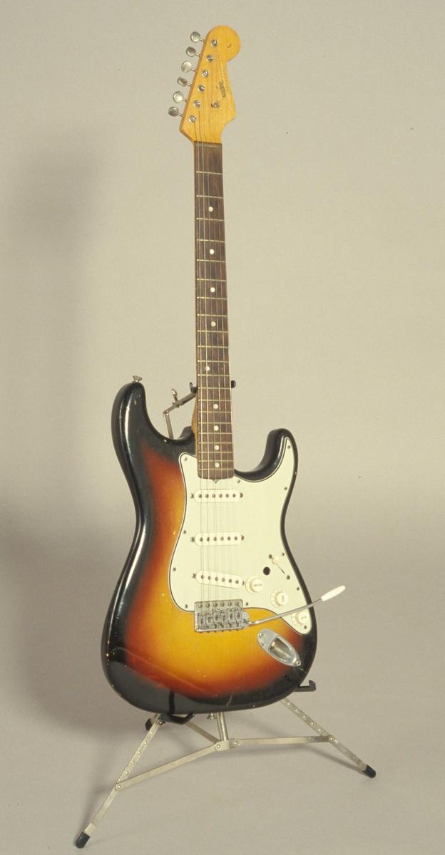 Elektrisk gitar, Fender Stratocaster, stående i gitarstativ.