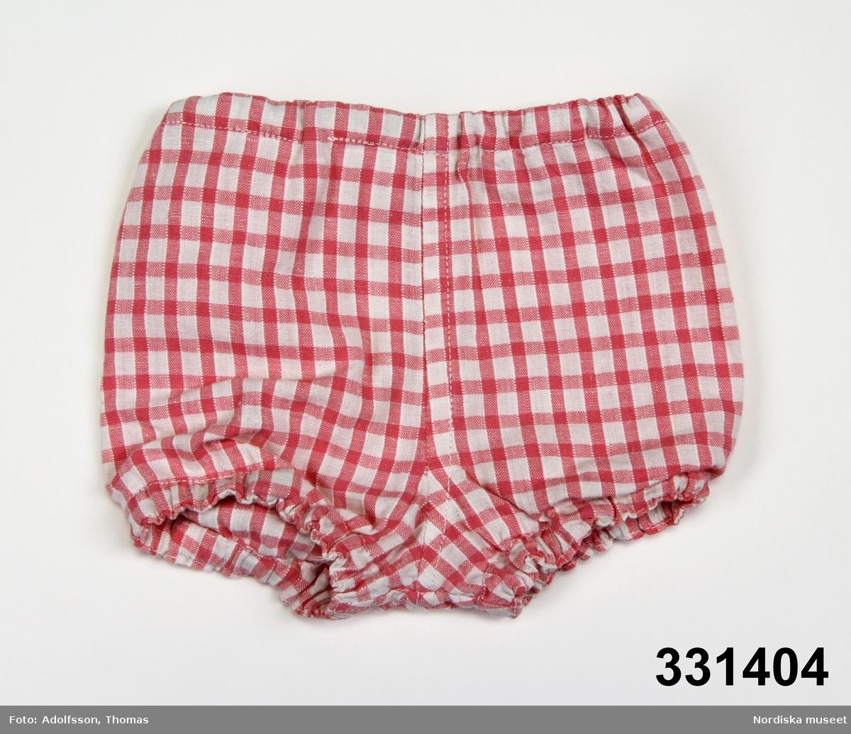 Ett par kortbyxor, rosa- och vitrutigt bomullstyg. Resår i benhål och midja. Liten hand för upphänning i linningen.  Matchande plagg NM.0331406-NM.0331408. /Karin Dern 2011-09-13