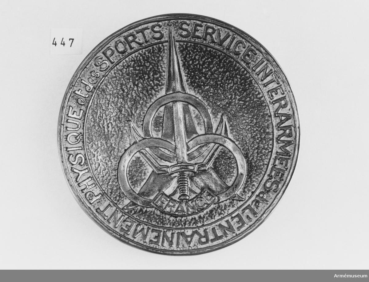 Tallriken är av brons (med imiterad ärg), och bär ett symboliskt sportmotiv och en inskription. På undersidan är fästade tre små fötter.