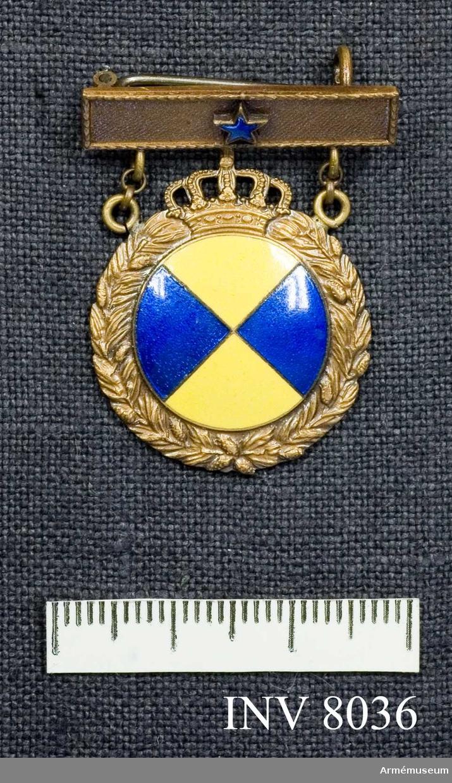 Samhörande gåva 8020-.  Idrottsmärke, ungdom, årtalsmärke. Märket hänger i ett spänne på vars platta en blåemaljerad stjärna sitter. I det runda märkets mitt är ett fyrdelat emaljerat märke, två gula och två blå delar. Tillverkare Sporrong. Höjd 2 mm (tjockleken). Längd 25 mm (plattan). Färg brons och blå och gul emalj.  Idrottmärket är instiftat av Svenska gymnastik- och idrottsföreningars riksförbund. Se Landsofficerssällskapets publikationer nr 1, 1930.