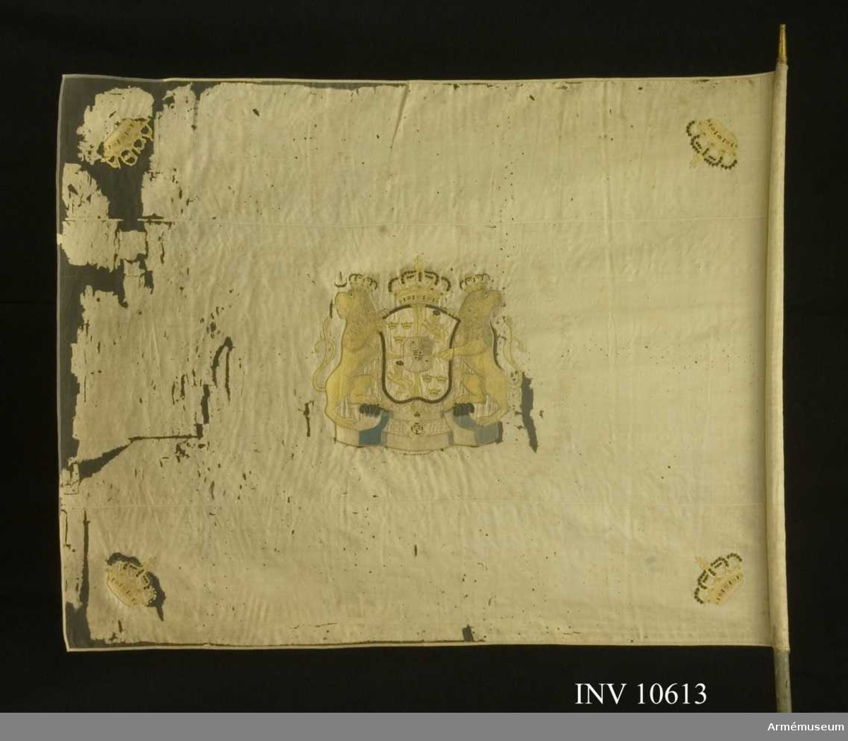 Grupp B.  Livfana. Duk av vit sidenkypert varå broderat å båda sidor, i  mitten svenska riksvapnet under Holstein-Gottorpska huset, skölden guldkantad, behängd med serafimerkedjan, krönt med  sluten kunglig krona i gult silke, med foder i rött silke och  pärlor i silver jämte de utåtseende, dubbelsvansade, med slutna kronor sköldhållande lejonen vilande på ett postament i blått  silke, i hörnen kronor liknande riksvapnets, kantad med vitt  sidenband, fäst med vitt sidenband och förgyllda spikar.Stång av furu, gråmålad, avsågad ovan fanan 22 mm, nedan 38. Holk av förgylld mässing.