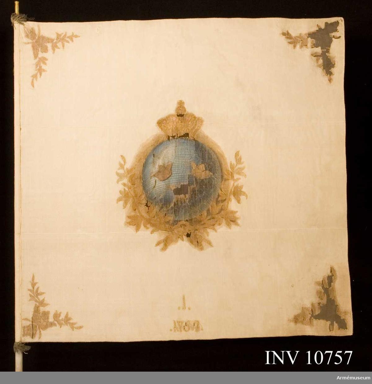 Fana, Stockholms Borgerskaps Infanterikår, 1 kompaniet. Grupp B I. Duk av vitt mönstrat siden med målade emblem. På den inre sidan lilla riksvapnet under sluten kunglig krona, därunder korslagda lagerkvistar. I de fyra hörnen korslagda lagerkvistar nedstuckna i öppna kronor, målat i guld med rödbruna schatteringar. På dukens nedre kant årtalet 1764, däröver en etta.   Riksvapnet har blå grund, kronan rött foder. På den yttre sidan Stockholms vapen S:t Erik, omgivet av en lagerkrans, allt under sluten kunglig krona målat i gult med rödbruna schatteringar. Kronans foder rött. I hörnen korslagda lagerkvistar nedstuckna i öppna kronor. På dukens nedre kant årtalet 1764, därunder en etta. Duken är kantad med guldsnodd som kring stången avslutas med en frans av 50 mm bred. Duken fasthålles av förgyllda spikar, därunder guldband.  Holken är av förgylld mässing och 80 mm hög. Spetsen av förgylld mässing med lilla riksvapnet höjd 188 mm. Stången är av furu, vitmålad, 1296 cm lång. Diametern vid fanans övre kant 29 mm och vid den nedre kanten 34 mm.