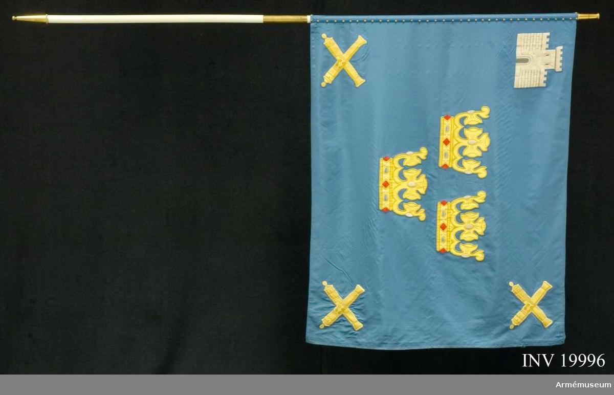 Duk av blått fansiden samt gult siden i intarsian. Broderi. Tre gula öppna kronor i fanans mitt, i övre inre hörnet Bodens fästning (Bodens kommuns vapenbild) och i de övriga hörnen tre gula korslagda eldrör. 40 st tännlikor.