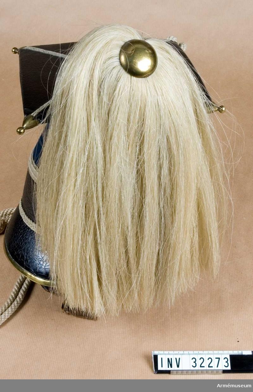 Grupp C I. Ur uniform för manskap vid Livgardet t häst; 1852-79. Består av vapenrock, epåletter, byxor, lansiärmössa, plym, stövlar, sporrar, halsduk, skärp, kartusch, kartuschrem,  handskar, sabelkoppel, sabel, balja, sabelhandrem. Enligt go 4/9 1852. Modellexemplar.