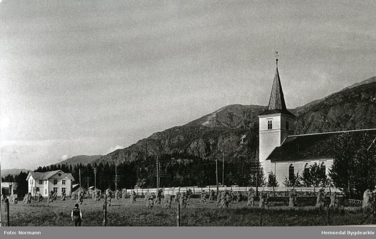 Hemsedal kyrkje med det gamle kommunehuset til venstre. Dette huset vart rive i byrjinga av 1980. I same området vart Kyrkjestugo sett opp i 1981. I framgrunnen ser ein korn på staur som var vanleg den gongen.