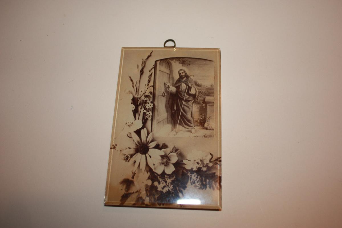 Bilde montert direkte på glas utan råme. Bakplate som er ledda slik at det kan stå på bord. Også oppheng for vegg. Trykket syner ein blomsterdekorasjon med eit bilde av Jesus med hyrdestav som bankar på ei dør.