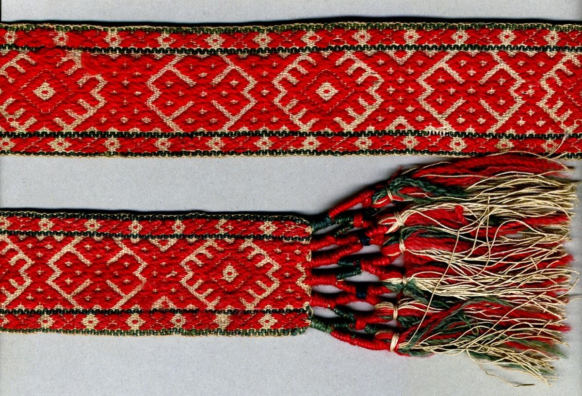 """Livband vävt i opphämta. Rött plockat mönster på oblekt linnebotten, två gröna tuskaftsränder längs kanterna. Avslutat i var ände med tofsar (130 mm långa); varptrådarna är omlindade med rött och grönt ullgarn vari frans av rött och grönt ullgarn samt halvblekt lingarn är iknuten. Varp, botten i halvblekt 2-trådigt s-tvinnat lingarn. Varp, mönster i rött och grönt 2-trådigt z-tvinnat ullgarn. Två bottenvarptrådar mellan varje mönstervarptråd. Inslag i halvblekt 2-trådigt s-tvinnat lingarn. Märkt med påsydd tyglapp med texten: """"Landstinget N° 30 a"""". Dessutom märkt med påsytt tygband med texten: """"SVENSK SLÖJD Malmöhus hemslöjd MALMÖ"""" och SHR-märke med texten: """"Nr 4 Herrestad"""". Längd inklusive tofsar."""