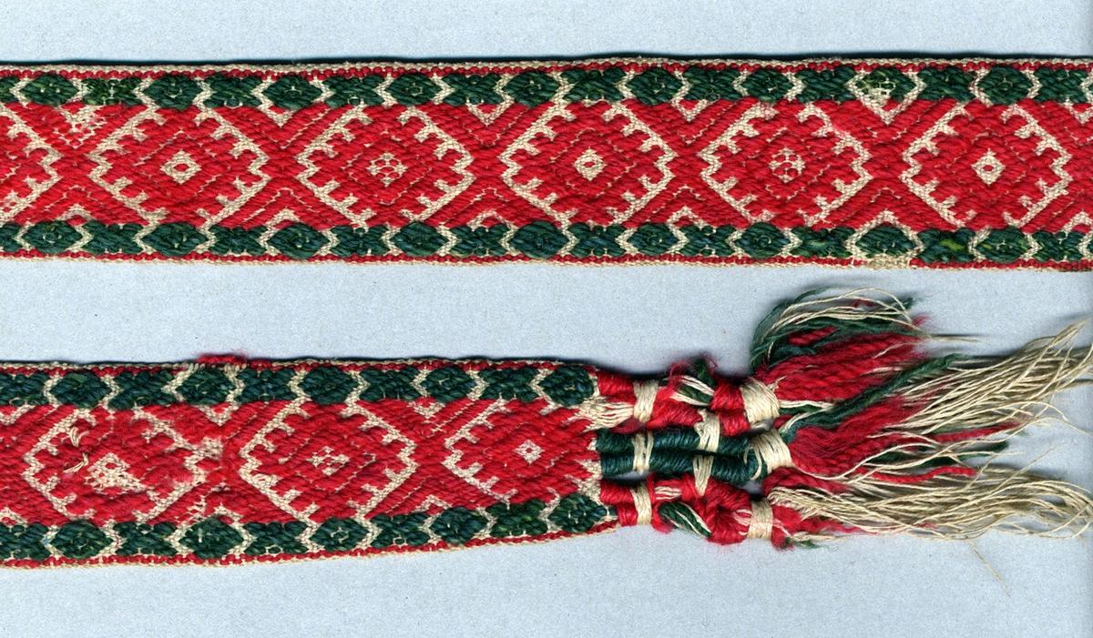 """Livband vävt i opphämta. Rött och grönt opphämtamönster på ljus botten; rött mitt på, grönt på var sida. Avslutat i var ände med tofsar (90 mm långa); varptrådarna är omlindade med rött och grönt ullgarn vari frans av rött och grönt ullgarn samt halvblekt lingarn är iknuten. Varp, botten i halvblekt 2-trådigt s-tvinnat lingarn. Varp, mönster i rött och grönt 2-trådigt z-tvinnat ullgarn. Två bottenvarptrådar mellan varje mönstervarptråd. Inslag i halvblekt 2-trådigt s-tvinnat lingarn. Märkt med SHR-etikett med texten: """"3,5 m"""". Längd inklusive tofsar."""