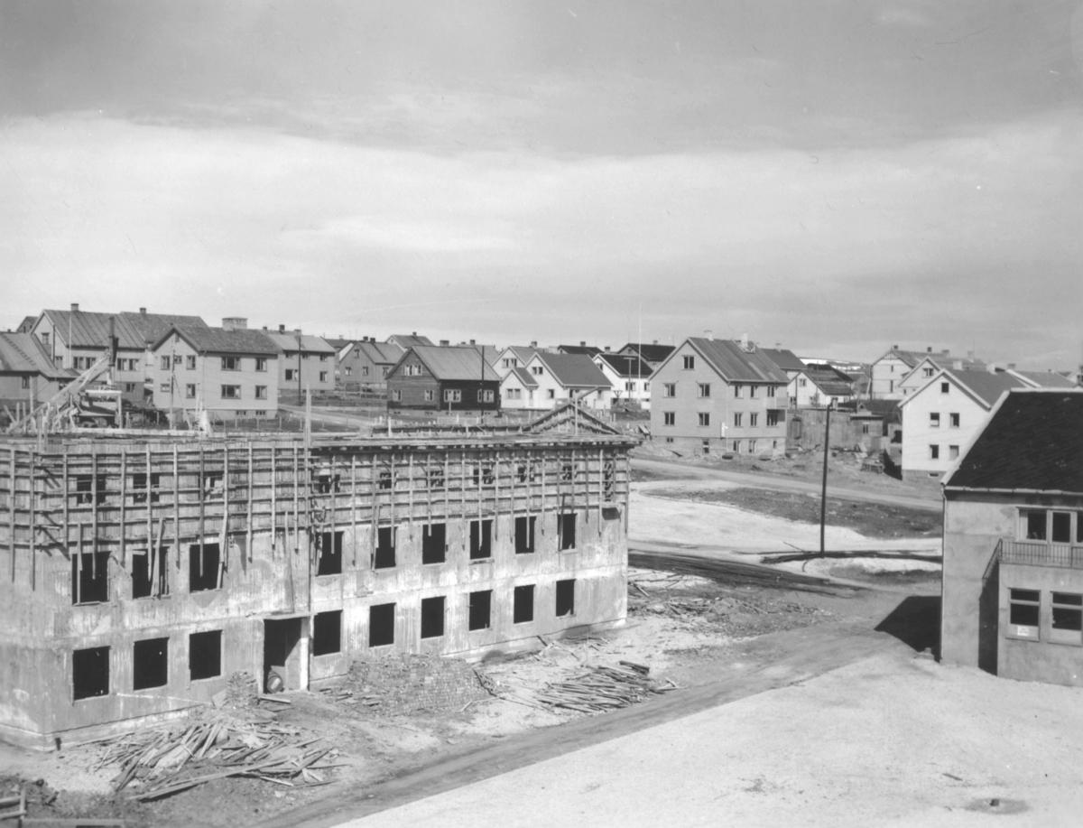 Rådhuset i Vadsø under bygging. Murbyggningen stod ferdig i 1952. Fremme i bildet ses en del av torget.
