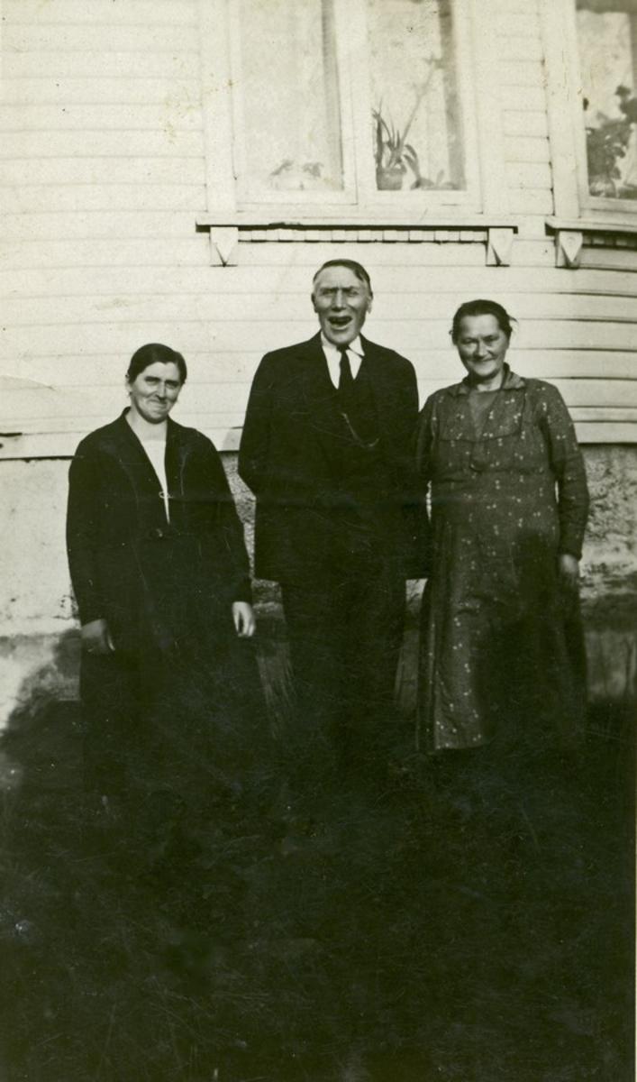 Tre personer foran bolighus