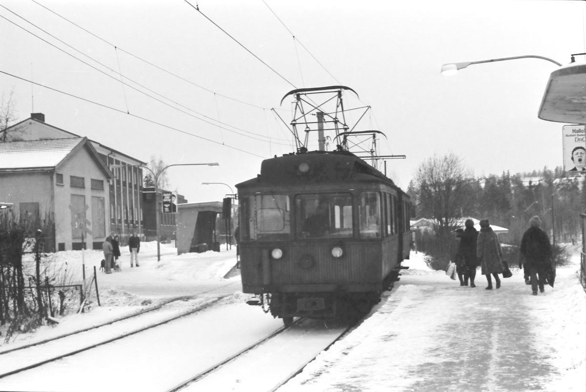 A/S Holmenkolbanen. Røabanen. Eiksmarka stasjon. Vogn 31, type 1909 (Skabo, Westinghouse, HKB verksted) på vei mot Østerås. I bakgrunnen til venstre ser vi en av banens likeretterstasjoner og Telegrafverkets telefonsentral.
