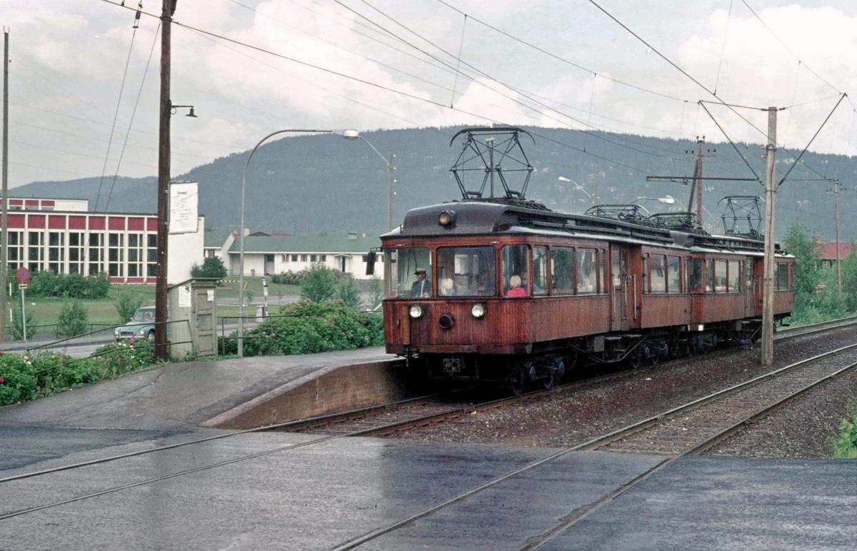 A/S Holmenkolbanen. Røabanen. Eiksmarka stasjon. HKB vogn 31 og 37, type 1909 (Skabo, Westinghouse, HKB verksted) på vei mot Østerås. Eiksmarka skole i bakgrunnen.