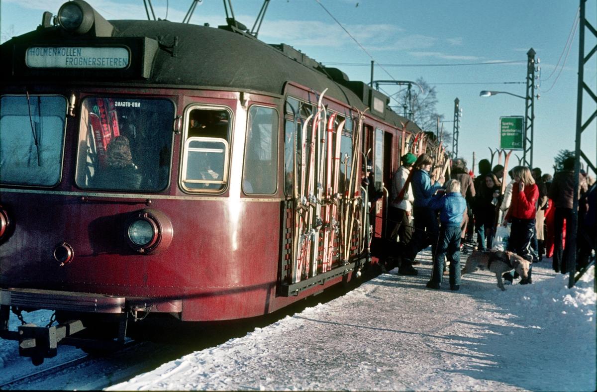 A/S Holmenkolbanen. Oslo Sporveier. Vogn 503, type 1946 (Skabo, NEBB). Reisende tar av ski fra skistativ på Frognerseteren.