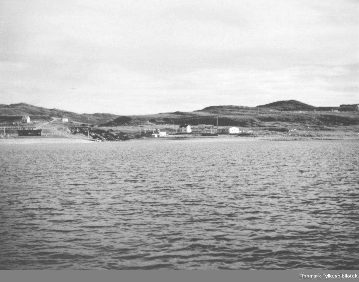 Bygninger i Kokelv sett fra sjøen. Nederst til venstre ligger skolebrakka. Oppfor ligger huset til Nils Andersen. På andre siden av veien står en garasje. Bygningen til høyre i bildet er Svendsens gjenreisningsbrakke. Bortenfor ligger boligen til Peder Nikodemusen. Overfor huset hans står det Nothjeller