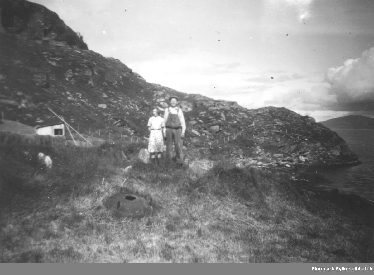 Peder Samuelsen, og hans datter? Leifine Bertine Nikolaissen står et stykke overfor fjæra. Et jordstykke er inngjerdet lengre opp. Peder er kledt i snekkerbukse, og skjorte. På hodet har han en skyggelue. Hun har en lys kjole på seg