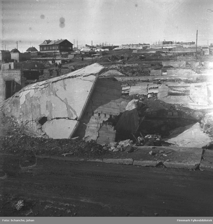 Ruiner i  sentrum av byen i 1946. Bak ruinene noen byggninger og brakkebyen.