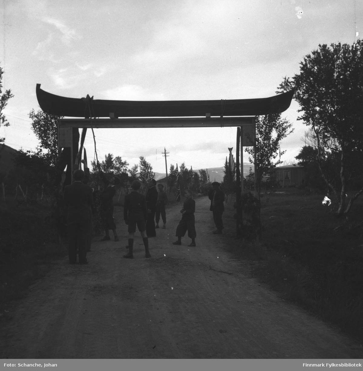 Kongebesøk: Kong Haakon VII besøker Tana.  Ã¿resport i Tana. En elvebåt ligger på toppen av porten. En gruppe unge gutter pynterporten med fisk (tørrfisk ?).