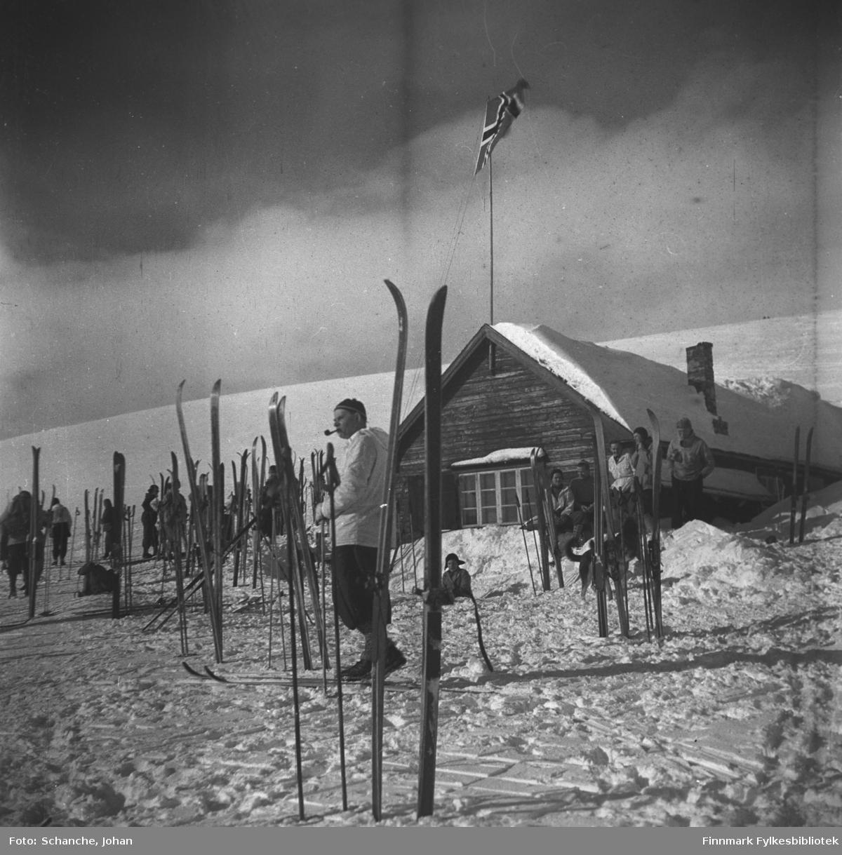 Vinikka skihytte fotografert en solig vårdag i 1946.  Flere skier står oppstillt på snøen rund hytta. Flaggen er heist opp og det går folk i anorakk bland skiene. Fremst på bildet står en mann og røyker pipa.