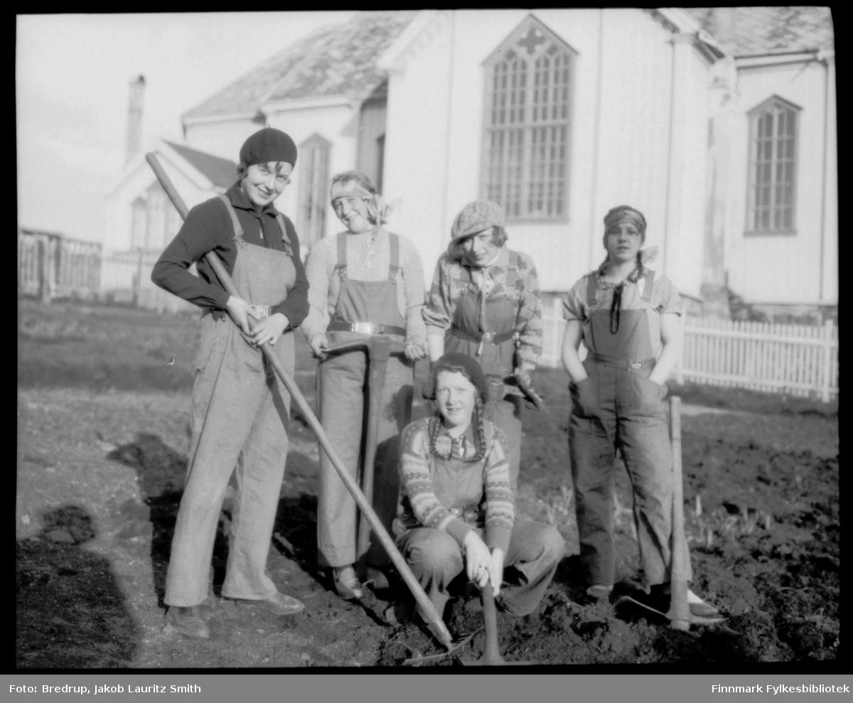 Fem unge blide kvinner jobber med hakker, raker og spader utenfor Vadsø kirke. Dette var del av et restaureringsarbeid på kirka. Fra Vadsø-kalenderen: 'Vadsø kirke som ble vigslet 3. oktober 1861.  En stilig og rikt utsmykket kirke, som hele byens befolkning var glad i, og der alle store høytider ble markert...Altertavla var en kopi av Adolf Tiedemanns maleri i Trefoldighetskirken i Oslo.  Under tyskernes tilbaketog, natten mellom 28. og 29. oktober 1944, brant kirka ned til grunnen.  Den nåværende Vadsø kirke ble vigslet palmesøndag 1958.'