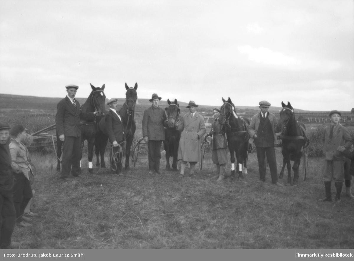 Fem hester med sulkyer stilt opp, sammen med eiere og kjørekarer.  Nysgjerrige gutter som tilskuere.  Tormod Holtis tekst: Bildet er tatt i 1933 og viser følgende fra venstre: Pandor (han var sjefsdreng hos kjøpmann Ole Nilsen i Vadsø og holder hesten 'Bravo II'), nummer to med ryggsekk er Helge Nilsen fra Masjok i Tana, nummer tre er Arnulf Bauna fra Skallelv, han holder hesten 'Stelle' sammen med nummer fire i frakk som er Sverre Larsen fra Boftsa i Tana, nummer fem er fru politimester Hofgaard med hesten 'Kavaler' og nummer seks er Einar Åstrøm fra Ekkerøy med 'Morgenstjerne'.  Ytterst til høyre er en yngre utgave av Heine Larsen.'