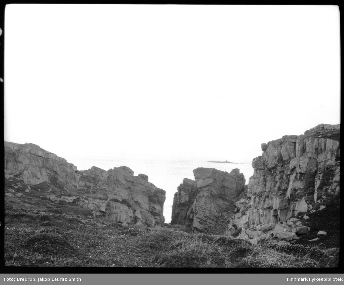 Forrevne steinformasjoner ned mot fjæra og sjøen.  Vi ser en holme med et seilingsmerke i bakgrunnen. Bildet er fra Finnmark et sted.