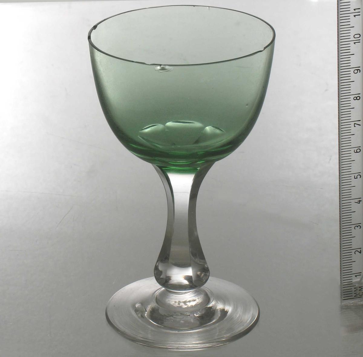 Rhinskvinsglass,  Klart  og grønt   glass.   Glatt  fot,   sekskantet stett ,  hvis slipninger ender den   rundbunnete, klokkeformete cupa begynne:  Vi klokke,   grønnfargen avtones mot munningen.  Grønnfargen er dypere enn 1930-årenes foretrukne lysere grønne.