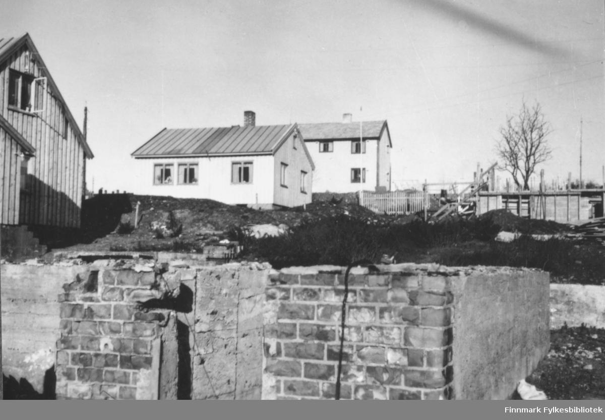 Bygninger og ruiner i Vadsø sentrum, september 1947. Gjenreisningen er i full gang etter at mesteparten av sentrum ble lagt i ruiner under andre verdenskrig. I forgrunnen står rester av en mur, i bakgrunnen ser man flere nybygg og til høyre i bildet står fundamentet til ett hus under bygging