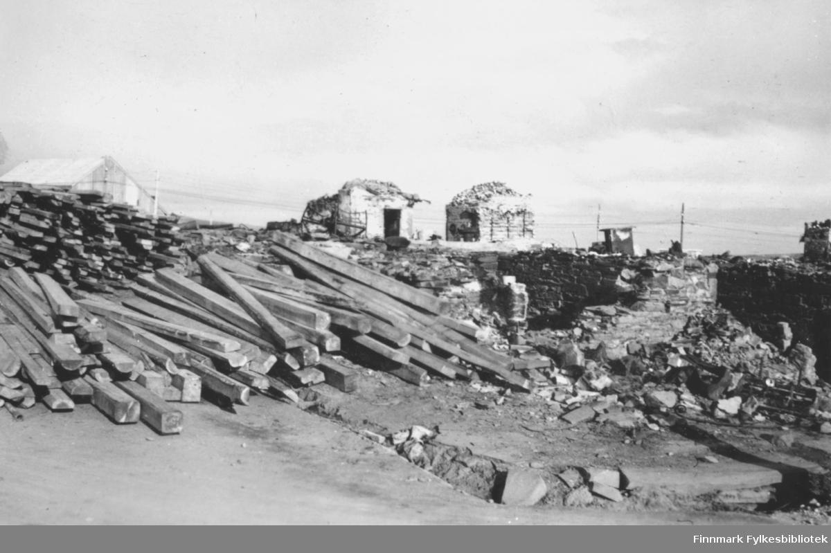 Fra Vadsø sentrum høsten 1946. Materialer har blitt fraktet inn for å starte gjenreisningen av alle bygningene som ble bombet under andre verdenskrig. I forgrunnen ligger hauger med treplanker oppå restene av en grunnmur. I bakgrunnen er det flere ruiner, en brakke og noen stolper