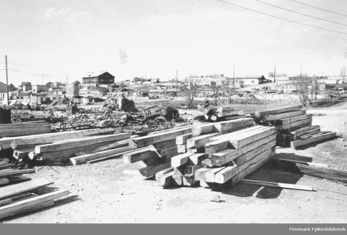 Materialer for gjenoppbygging av Vadsø sentrum ligger på en tomt med ruiner i bakgrunnen. Mesteparten av sentrum lå i ruiner etter bombingen under andre verdenskrig. I bakgrunnen ser man flere tomter med ruiner, og endel stolper med elektrisitetslinjer mellom. Det ligger et intakt hus oppå høyden, samt noen brakker lenger bak i bildet
