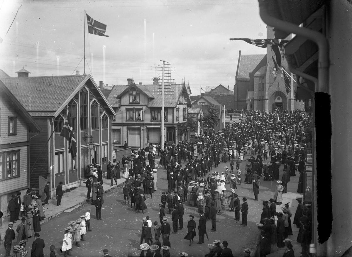 Folketog fra Vår Frelses kirke og vestover den 13.august i 1905 i anledning folkeavstemningen om oppløsningen av unionen med Sverige. Trehus til venstre og i bakgrunnen. Noen norske flagg. Flere personer på gaten.