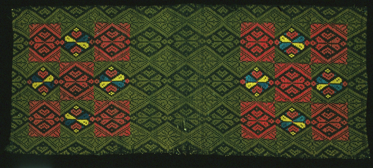 """Längd eller framstycke till dyna vävd i opphämta på botten i inslagsrips. Svart botten med mönster av snedställda rutor och hjärtformer över hela ytan. Genom färgbyten bildas två fält i var sida med kvadrater i blårött samt mönster i blått och gult. Fållad i kortsidorna med lintråd. Stadkanter i långsidorna. Varp i oblekt 2-trådigt s-tvinnat lingarn, 68 trådar/10 cm.Botteninslag i natursvart 1-trådigt ullgarn, ca 32 inslag/cm. Mönsterinslag i grönt och rött 2-trådigt z-tvinnat ullgarn eller gult och blått dubbelspolat 1-trådigt z- och s-spunnet ullgarn. Märkt på baksidan med påsydd tyglapp med texten: """"Landstinget N° 119 a Skytts H-d""""."""