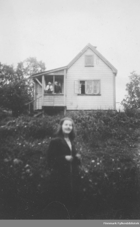 Torill Stene - i bakgrunnen ser vi ei hytte med flere personer på verandaen