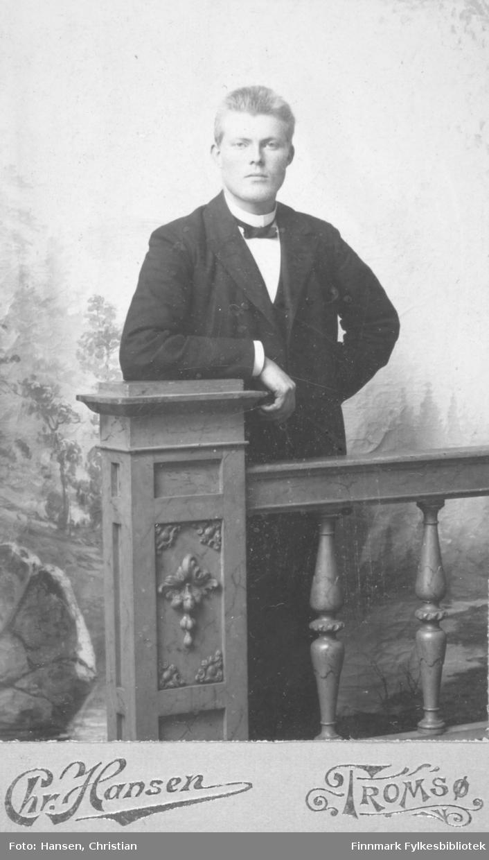 Portrett av en ung mann. Navnet er ukjent. Han er kledd i mørk dress skjorte med stiv snipp og sløyfe. Fotografert i fotoatelier med håndmalt bakgrunn. Fotograf Chr. Hansen i Tromsø har tatt bildet.