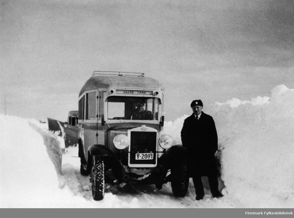 A/S Polarbil (y-2091, Volvo) brøyter veien, riksvei 950, Vadsø-Varangerbotn. Ved siden av bussen står en mann som heter Gustav A. Junge og en mann sitter i bussen (vi vet ikke navnet). I bakgrunnen ser man litt av brøytebilen. Se også bildene 577-588. A/S Polarbil var et rutebilselskap som eksisterte i tidsrommet 1920-1976. Ruteområdet dekte hovedstrekningene i Øst-Finnmark. Polarbil hadde hovedkontor i Vadsø. 1. januar ble selskapet med rutekonsesjoner, ansatte og bilmateriell overtatt av Finnmark Fylkesrederi og Ruteselskap (FFR).