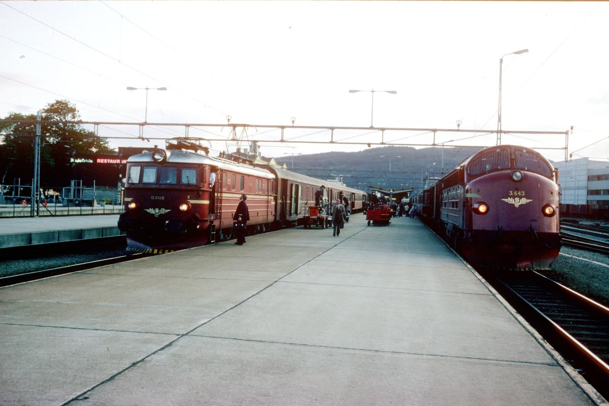 Ekspresstog 45 med NSB elektrisk lokomotiv El 11 2082 har ankommet Trondheim fra Oslo S. Dubleringsnattoget, tog 453 til Bodø står klar med Di3 643. Disse togene var tog som bare ble kjørt om sommeren og ved høgtider.