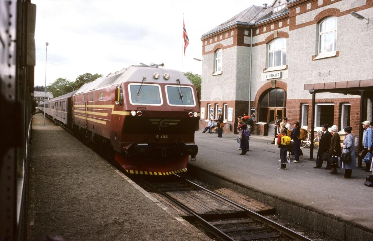 Sørgående dagtog på Nordlandsbanen, hurtigtog 452, ankommer Steinkjer med dieselelektrisk lokomotiv Di 4 655. Bildet er tatt fra kryssende tog, persontog 457 til Grong med dieselmotorvogn type 86.