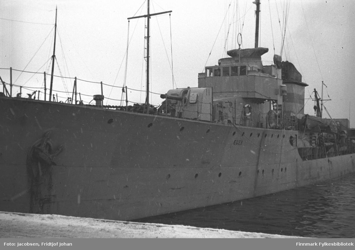 Jageren Ã¿ger ved kai i Hammerfest. Båten er grå og en stor kanon ses på fordekket. Bak kanonen står rorhuset med skorsteinen rett bak. En liten del av den snødekte kaia ses nede på bildet.