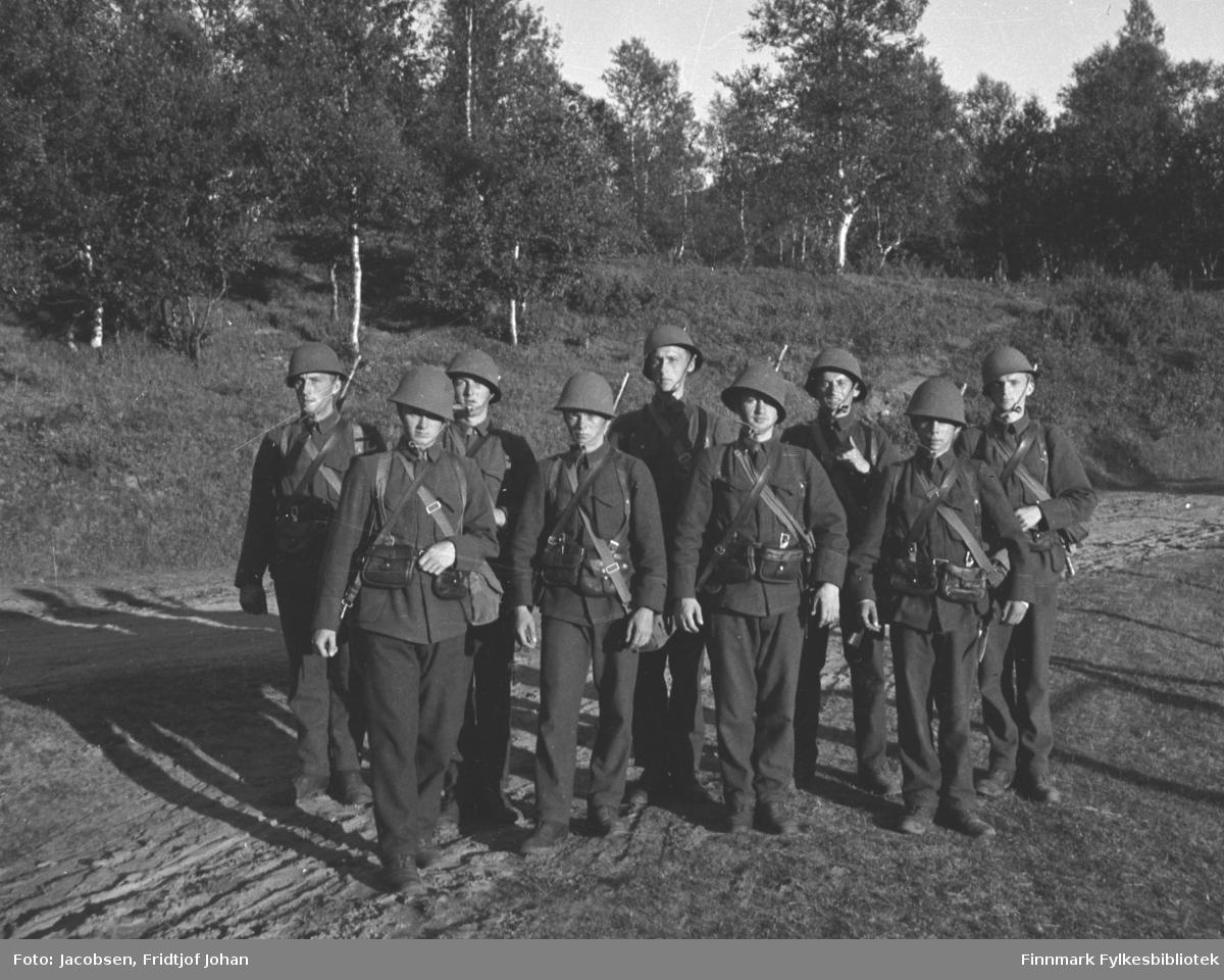 En gruppe soldater (nøytralitetsvakter) i fullt feltutstyr. Fridtjof Jacobsen står helt til høyre. Alle er iført mørke uniformer og har hjelmer på hodet. De står på en liten slette med stort sett sand- og gressdekke. En liten gressdekt skråning med mye løvtrær i bakgrunnen. Bildet kan være tatt i Alta i forbindelse med Jacobsens militærtjeneste eller en øvelse han deltok i.