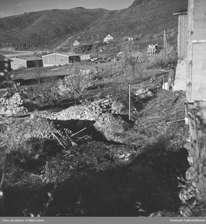 Kloakken graves fra eiendommen til Arne og Sigrid Nakken i Rypefjord. En person står med ryggen til kamera ved grunnmuren til høyre på bildet. Grøfta ses midt på bildet og en liten stabel med steiner står helt til venstre på bildet. Flere små trær og busker står i hagen som ellers har gressdekke. Flere bygninger og noen snøskjermer står på området.
