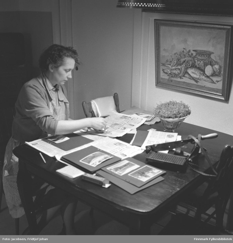 Aase Jacobsen sitter ved spisebordet hjemme i Storvannsveien og limer fotografier i album. På bordet ligger flere albumsider og avissider. En papirkutter og esken til en limtube ligger også der. Aase har en ganske lys, tynn genser og et stripet forkle på seg. En blomsterdekorasjon står på bordet og et maleri henger på veggen rett over spisebordet. Nederste delen på en taklampe ses øverst på bildet.