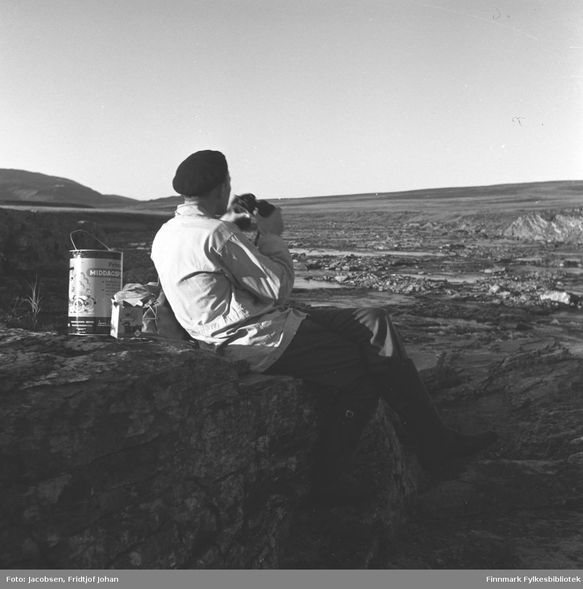Alf Edvard Jacobsen på jakt etter multebær på Sennalandet. Han har en mørk bukse, lys jakke og sort lue på seg. Han sitter på en stor, flat stein og har en kikkert i hendene. Et metallspann og en liten pappeske står like bak han. Det flate Sennalandet ses over store deler av området, men en fjelltopp står helt til venstre på bildet.