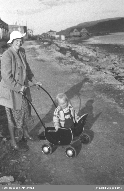 Farmor Olga Jacobsen på tur med barnebarnet Arne i barnevogn. De er på besøk i Havøysund hos Arnes far, Fridtjof Jacobsen. Olga er iført en hvit/lys hatt, ganske lys kåpe, mønstret skjørt og små, forholdsvis mørke sko. Arne står i barnevogna og har en mørk snekkerbukse, mønstret strikkegenser og stripet skjorte på seg. Vogna han står i er mørk/sort og har ganske små hjul med blanke hjulkapsler og et langt, sortlakkert håndtak. De er fotografert på en grusvei. Sola skinner og kaster skygge av dem. Flere bygninger står på venstreside av veien. Til høyre er fjæra med stein og litt av havet ses oppe til høyre. Over sundet står et fjellparti som vises ganske mørkt på bildet.