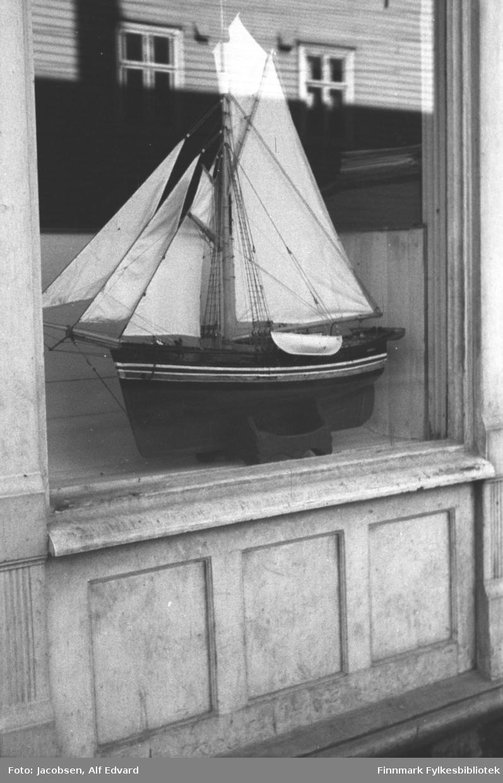 Modell av en seilskute i et utstillingsvindu. Båten er malt i en mørk farge med en lys stripe oppe mot rekka. En hvit/lys livbåt henger på siden. Båten har flere seil, et stort bak og tre mindre foran. Det har endel tauverk og leidere fra mastene og mot rekka. Stativet båten står på er i samme farge som skroget. Vinduet har et avrundet vannbrett under og tre speil på veggen.