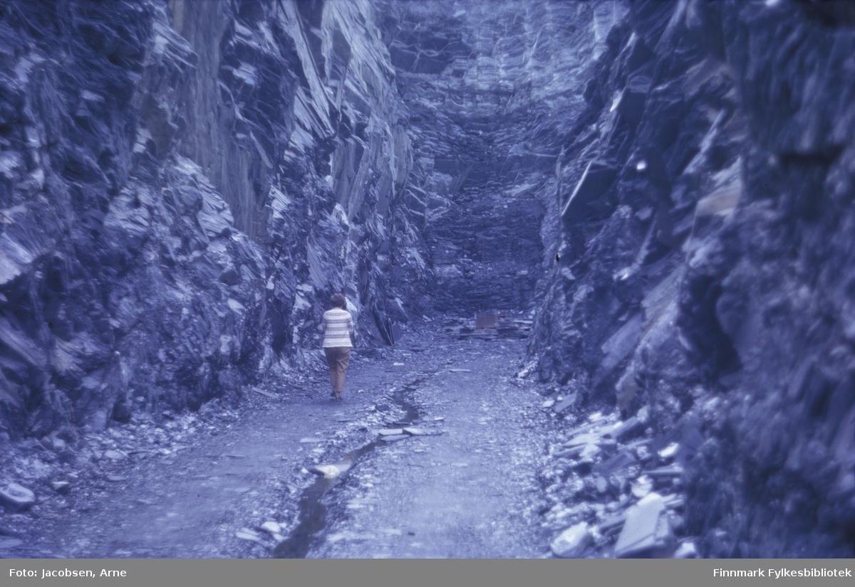 Aase Jacobsen på tur i et stein-/skiferbrudd. Hun har lyse bukser og lys, stripete genser på seg. En anleggsvei går bortover, men stopper brått der fjellveggen begynner midt på bildet. Begge sidene består av høye steinvegger med mindre steiner liggende langs sidene.