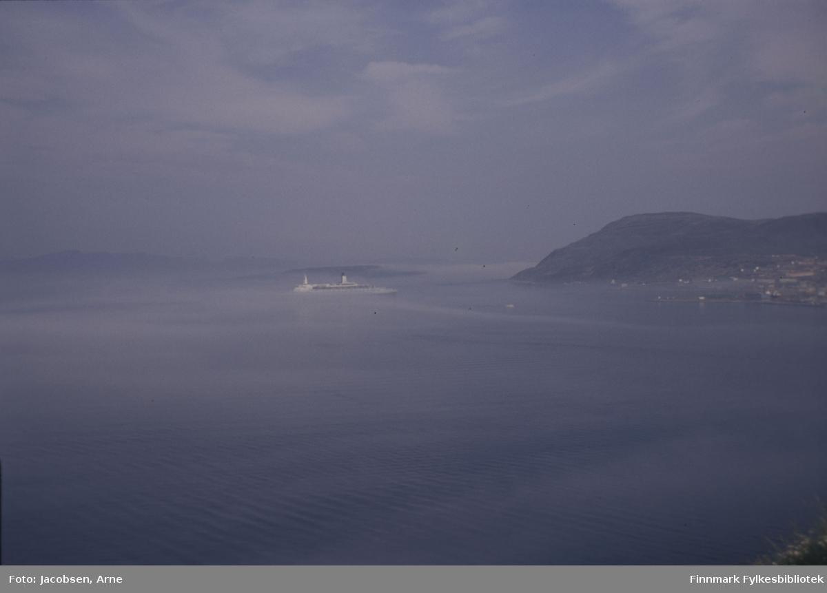 Turistskip på vei inn mot Hammerfest. Det er endel tåke, men Melkøya, Melkøysundet og Sørøya kan skimtes rett bak skipet. Været er ellers bra med lite vind og opphold. Til høyre i bildet ses noe av bydelen Fuglenes med fjellet Vardfjell i bakgrunnen. Bildet er nok tatt fra området Storsvingen