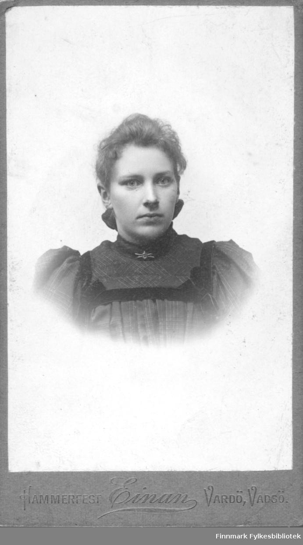 Portrett av en ung ukjent kvinne. Hun er kledt i en mørk kjole eller bluse som er pyntet med fløyelsbånd. I halsen har hun en brosje