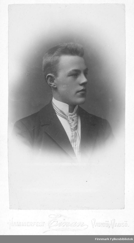 Portrett av en ukjent ung mann. Han er kledt i en mørk jakke og hvit skjorte. Han har et lyst, stripet slips i halsen
