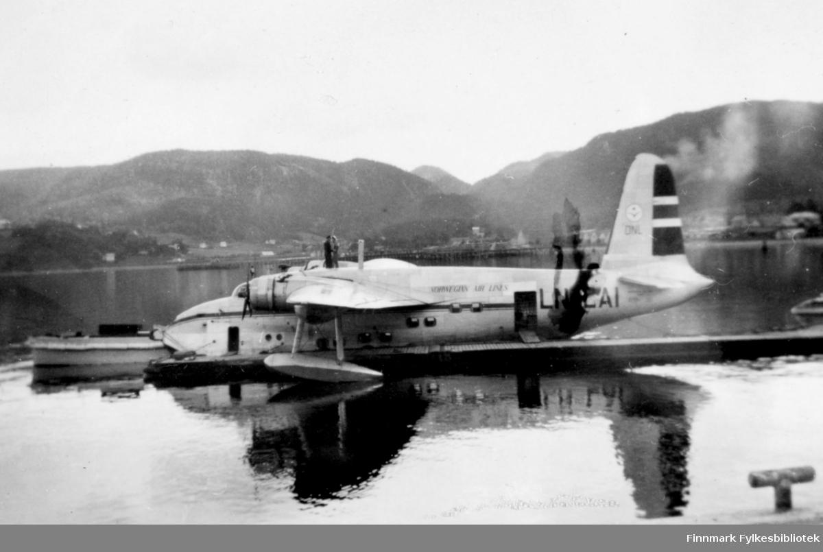 """Flybåten DNLs Short Sandringham LN-LAL """"Jutulen"""" ligger ved en flytebrygge. På taket står to personer. Foran flybåten er det en åpen båt på vannet. I bakgrunnen er det fjell og spredt bebyggelse."""