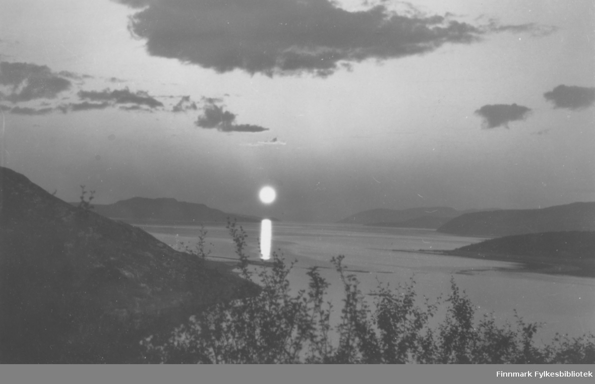 Fotografi fra en fjord omgitt av fjell. På bildet speiler sola seg i sjøen. Himmelen har noen mørke skyer. I forgrunnen av bildet er det trær