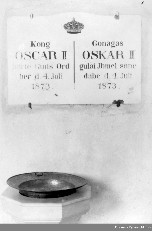 Fotografi av interiør inne i Kong Oscars II kapell som er bygget i 1869. På bildet ser vi en døpefont. Karret er laget av metall. På veggen oppfor henger en tavle. Det er bilde av en krone øverst. På venstre side er det skrevet 'Kong Oscar II hørte Guds Ord her d. 4. Juli 1873'. På høyre siden er det samme skrevet på samisk. Kong Oscar II besøkte kirken og etter det har kirken båret hans navn